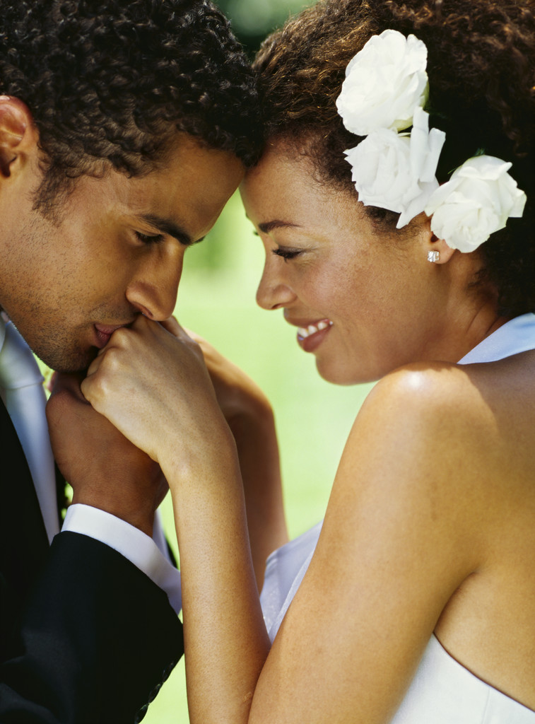 side profile of a groom kissing his bride's hands
